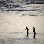 Two local fishermen fishing at dusk in Tabatinga, Amazon rainforest, Colombia